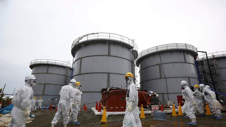 Members of the media and TEPCO employees wearing protective suits and masks walk past storage tanks in Fukushima prefecture