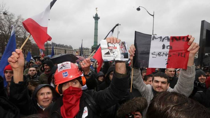 A demonstrator displays a leaflet which reads 'Hollande Resign' during unrest in Paris.
