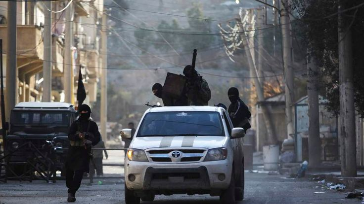 Members of the Islamist Syrian rebel group Al Nusra Front ride on a vehicle mounted with an anti-aircraft weapon, along a damaged street in Deir al-Zor