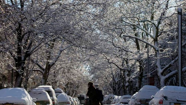 A woman crosses a slush and snow covered street in the Park Slope section of Brooklyn