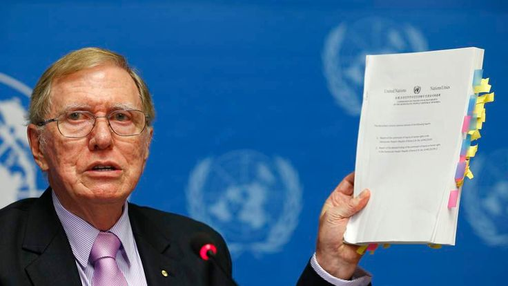 Kirby, Chairperson of the Commission of Inquiry on Human Rights in North Korea holds a copy of his report during a news conference at the United Nations in Geneva