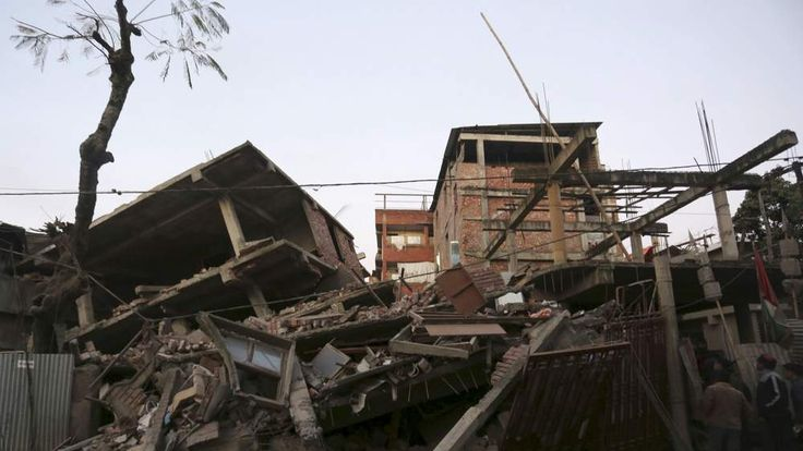 People look at damaged residential houses after an earthquake in Imphal.