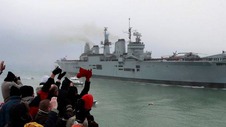 Crowds wave to the aircraft carrier HMS Ark Royal as she enters harbour for the final time ahead of decommissioning in Portsmouth southern England