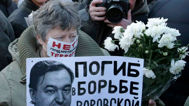 A woman holds a placard with a portrait of Sergei Magnitsky during an unauthorised rally in central Moscow