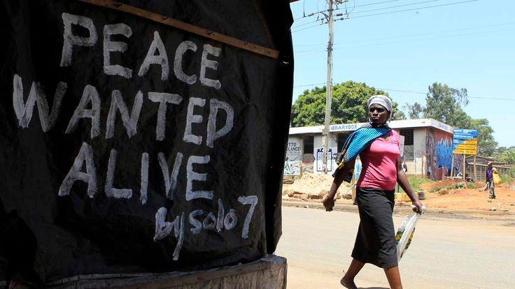 A woman walks past a message of peace in Kibera slum in the capital Nairobi.
