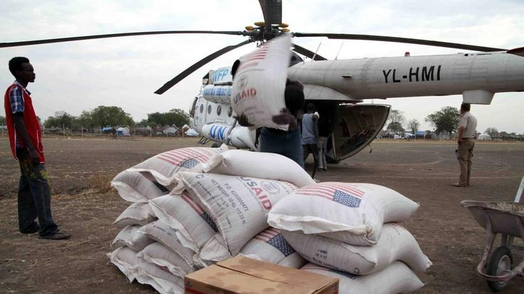 People unload aid from an UN helicotper