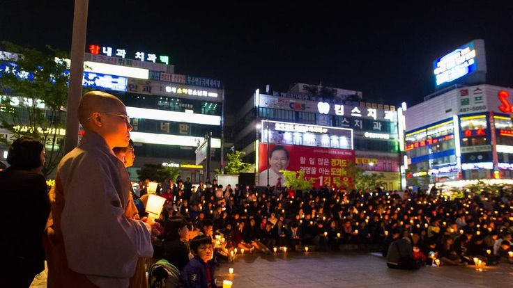 People hold candles at a vigil in Ansan for those missing in the capsized ferry