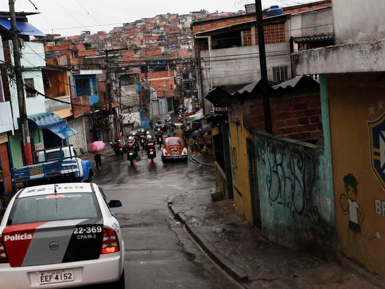 Police in cars and on motorcycles drive past graffiti (R) referring to the Brazil Soccer Federation (CBF) at the Brasilandia favela