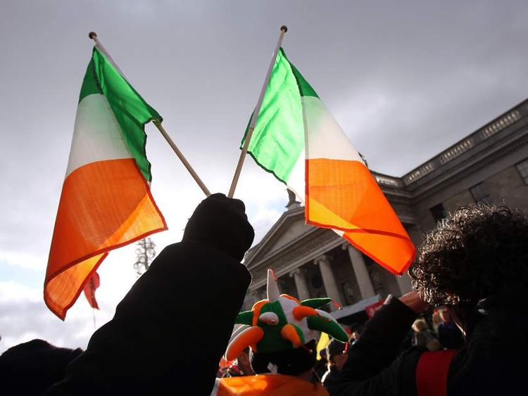 A protester holds up two Irish flags in.