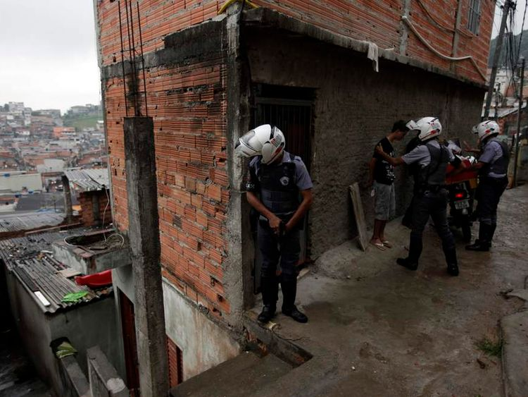 Police officers frisk residents of the Brasilandia favela