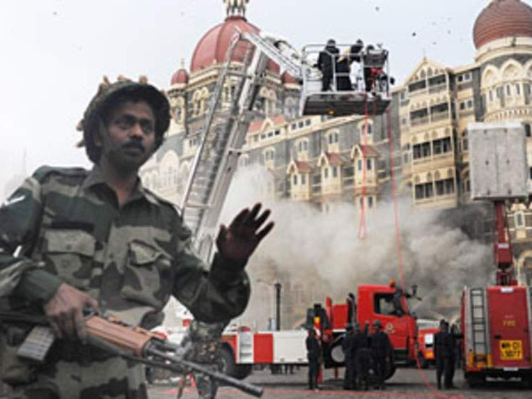 An Indian soldier prevents people from aproaching the The Taj Mahal Hotel after a rescue operation in Mumbai