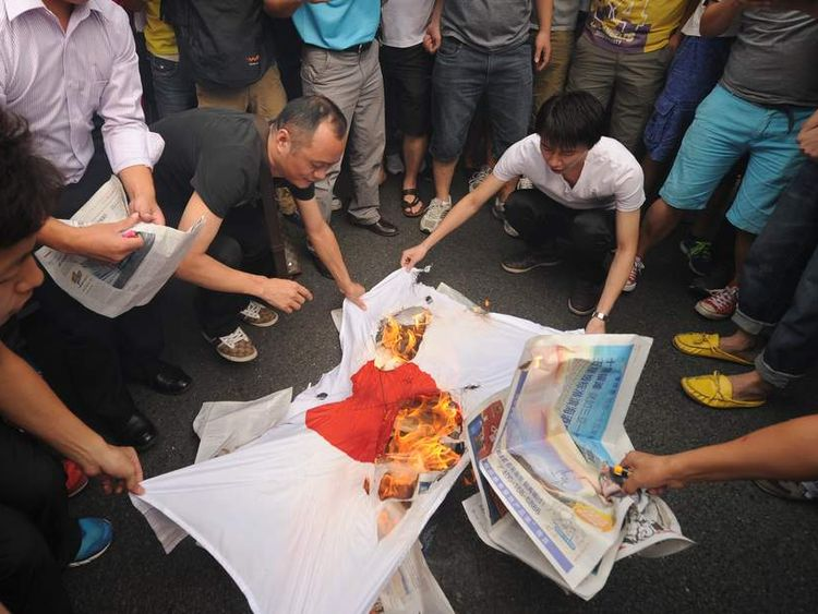 Anti-Japan protesters burn a Japanese national flag during a protest over the Diaoyu islands issue, known as the Senkaku islands in Japan, in the southern Chinese city of Shenzhen on September 18, 2012.