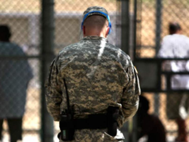 A guard watches over Guantanamo detainees inside the exercise yard at Camp 5.