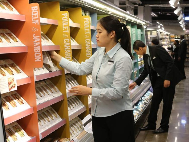 Employees arrange products on shelves at a French Marks & Spencer store