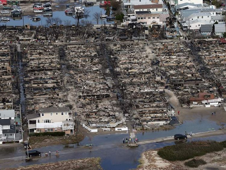 People gather around the remains of burned homes after Superstorm Sandy in the Breezy Point neighborhood of the Queens borough of New York City