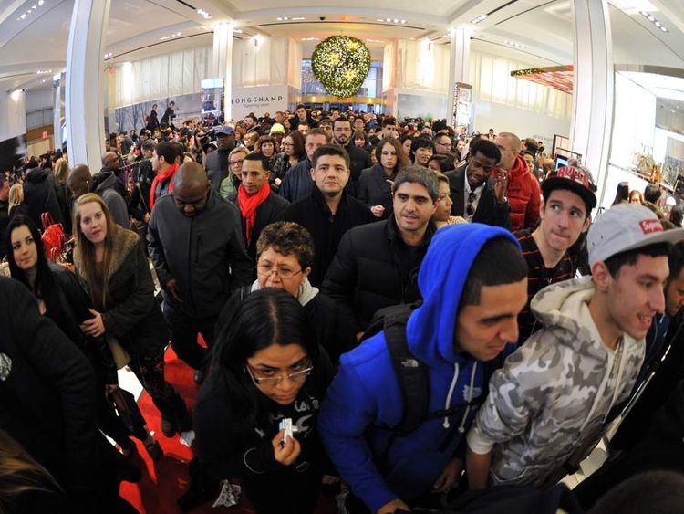 People rush into Macy's department store as they open at midnight