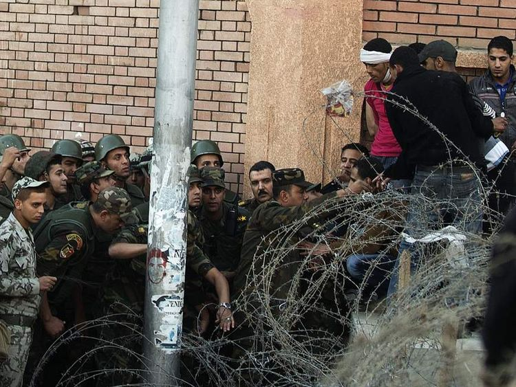 Egyptian soldiers stop demonstrators from crossing a barbed wire fence