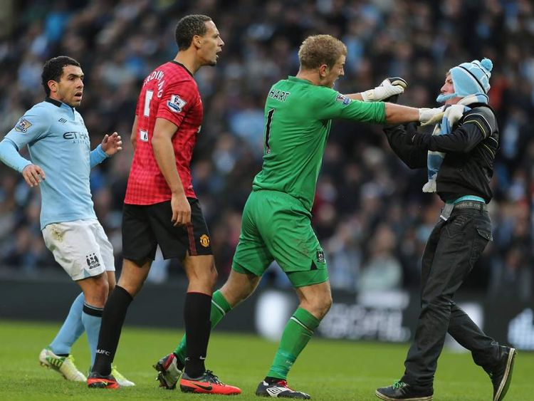 Rio Ferdinand of Manchester United, Joe Hart and Carlos Tevez of Manchester City apprehend a pitch invader