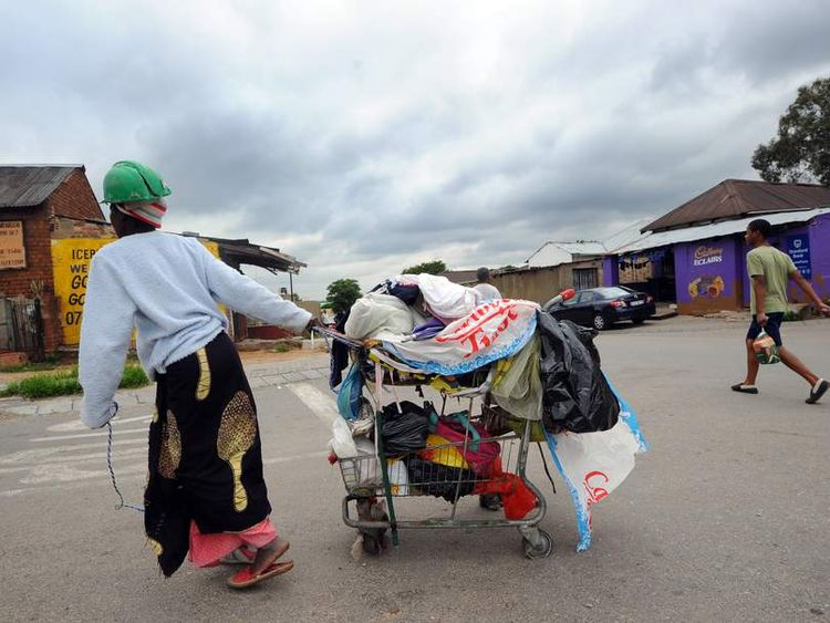 A woman carrying her cart through Alexandra township