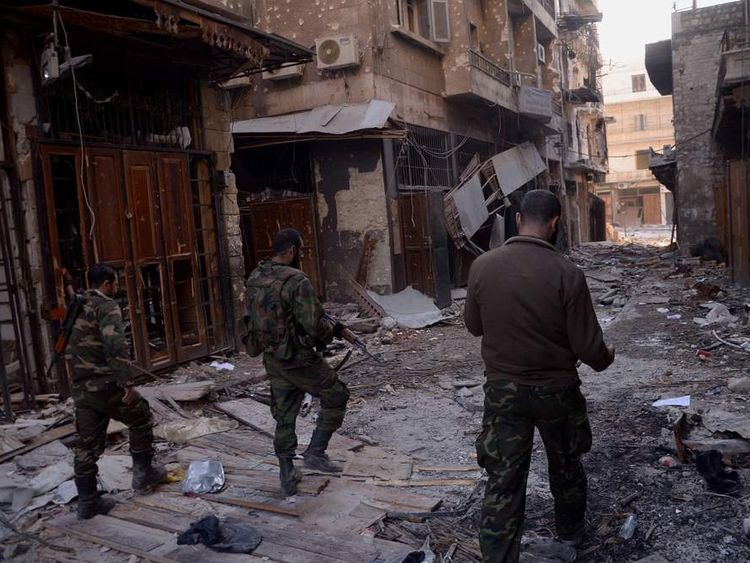 Syrian government forces walk through the destruction in the old souk of the northern Syrian city of Aleppo after they allegedly recaptured the area from opposition forces.