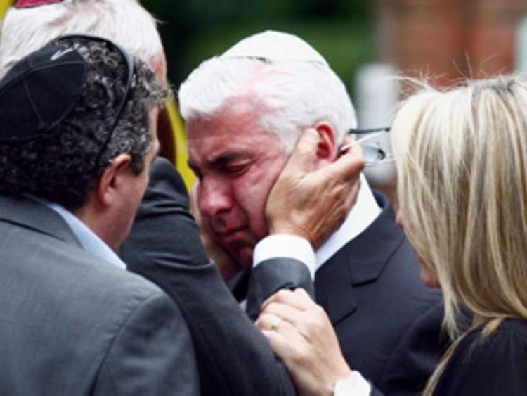 Father of Amy Winehouse, Mitch, (centre) is consoled outside Golders Green Crematorium in north London