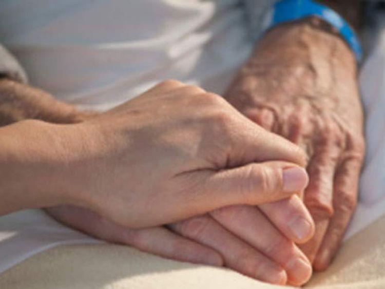 Nurse holding elderly mans hand