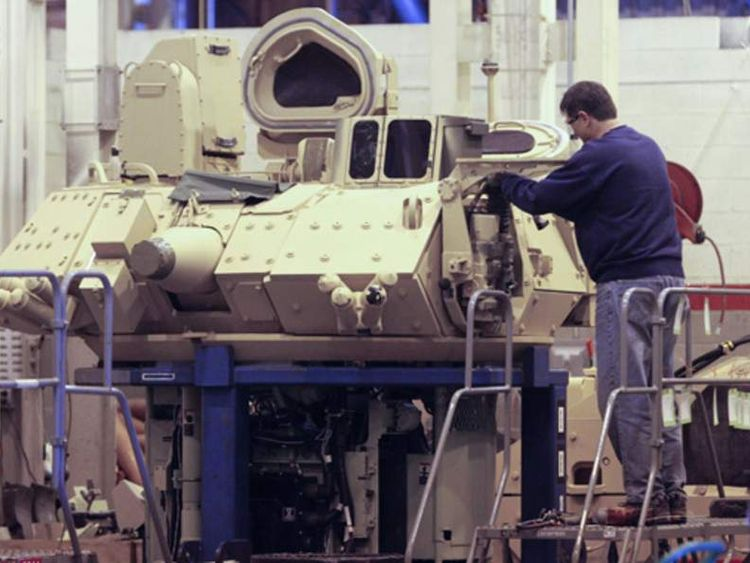 A BAE Systems technician works on a turret for a Bradley fighting vehicle