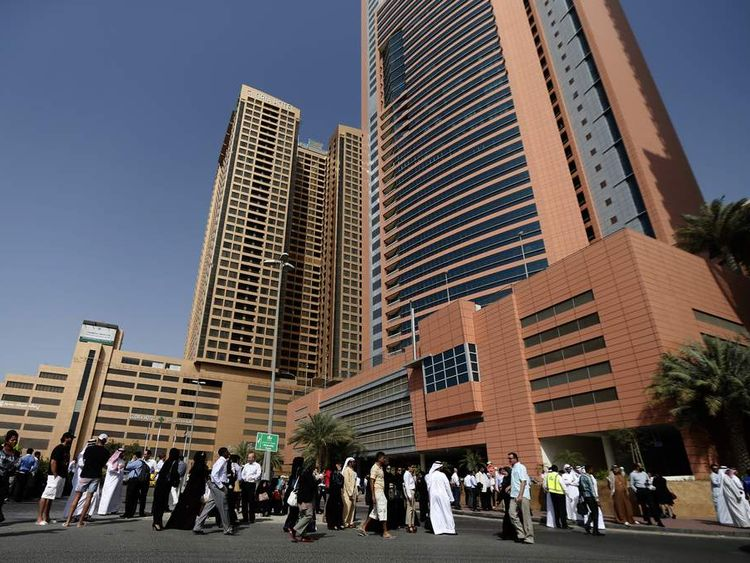Employees gather outside high-rise buildings in Dubai after a powerful earthquake struck Iran