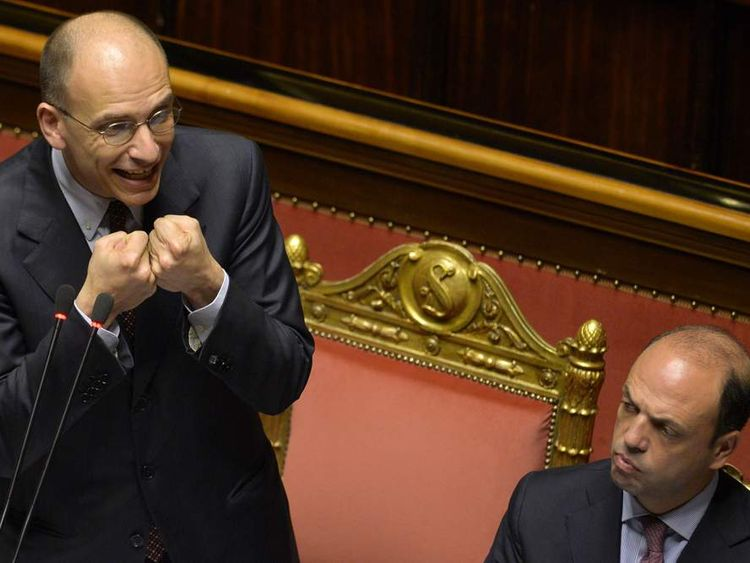 Enrico Letta (L) delivers a speech