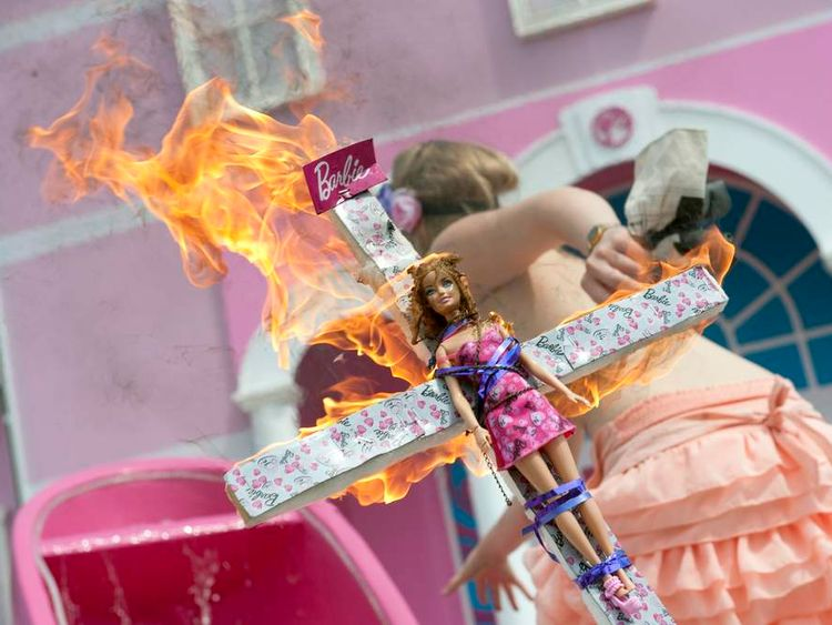 A Femen activist holds a burning crucifix with a Barbie doll fixed on it as she runs during a protest action in front of the so called Barbie Dreamhouse in Berlin