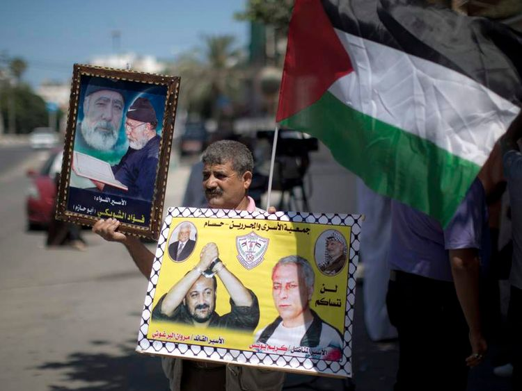 A Palestinian man holds placards featuring Palestinian prisoners