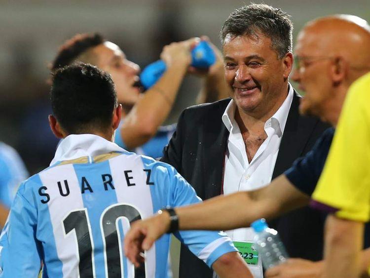 Argentina's Leonardo Suarez is greeted by his coach Humberto Grondona