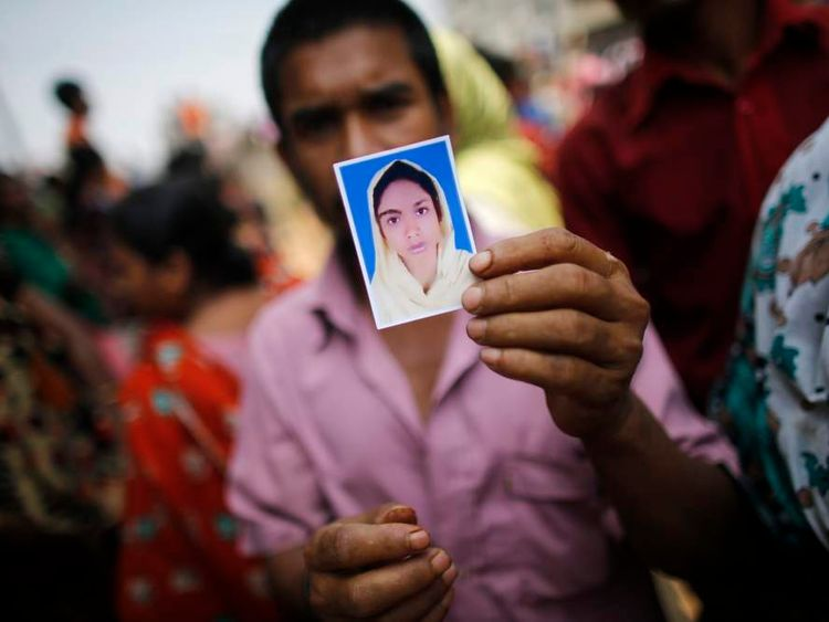 A relative holds a picture of a missing garment worker, who was working in the Rana Plaza when it collapsed, in Savar