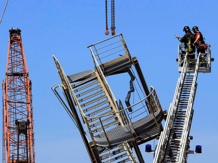 Firefighters look at a part of the collapsed control tower at the port in Genoa