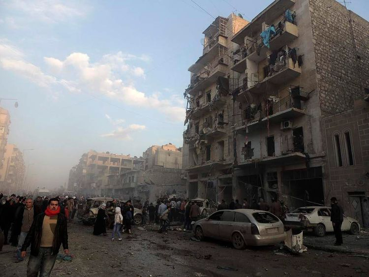 People gather at a site hit by what activists said were barrel bombs dropped by government forces in Aleppo's Dahret Awwad neighbourhood