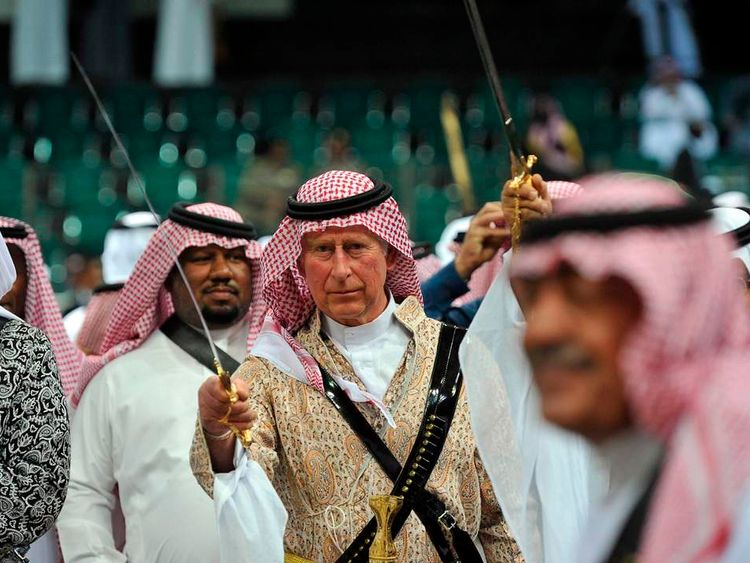 Britain's Prince Charles, wearing a traditional Saudi uniform, dances with a sword during the a traditional Saudi dancing, known as 'arda', which was performed during Janadriya culture festival at Der'iya in Riyadh