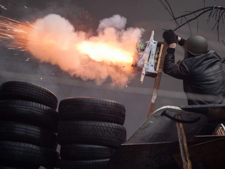 An anti-government protester shoots an improvised device during clashes with riot police in the Independence Square in Kiev