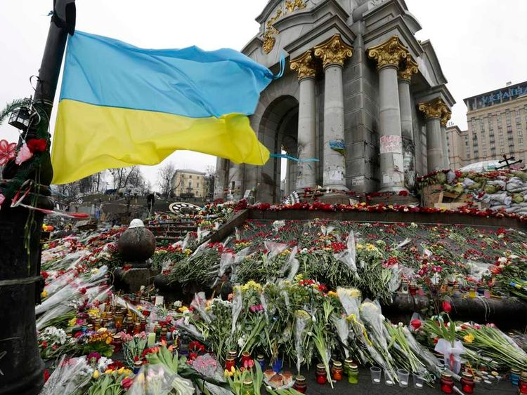 Ukraine's national flag flies at a make-shift memorial for those killed in recent violence in Kiev