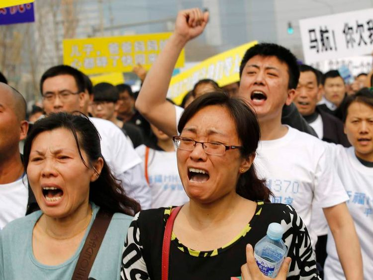 Family members of passengers on board Malaysia Airlines MH370 shout during protest in front of Malaysian embassy in Beijing