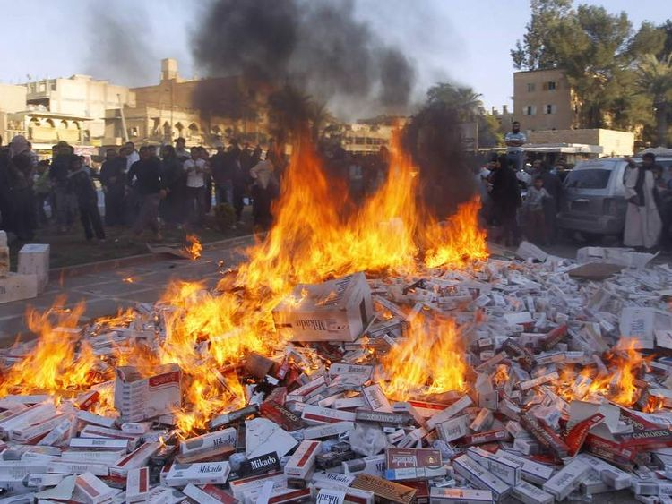 Fighters from Islamic State in Iraq and the Levant burn confiscated cigarettes in the city of Raqqa