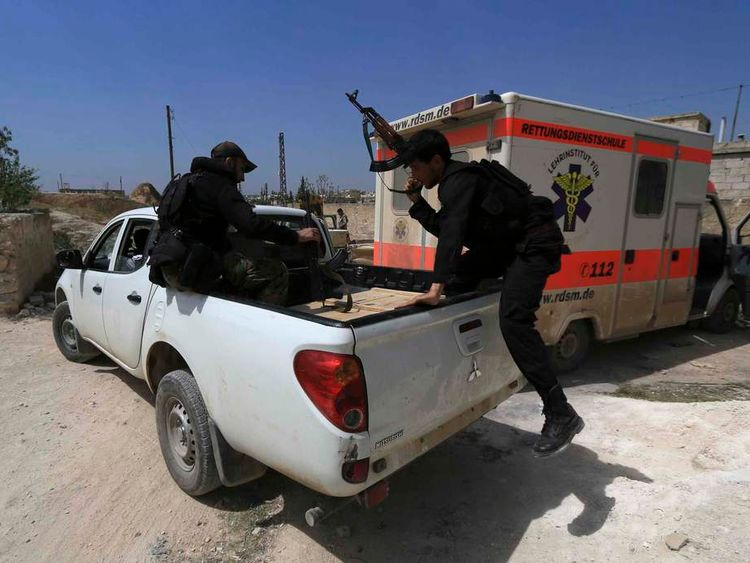 A rebel fighter jumps into vehicle as he and fellow fighters head towards positions in Heesh village in Idlib