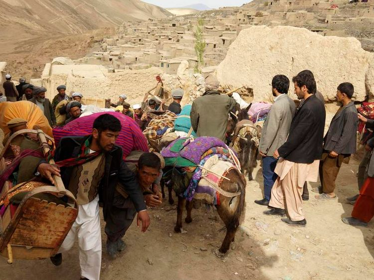 People walk with their belongings near the site of a landslide at Badakhshan province.