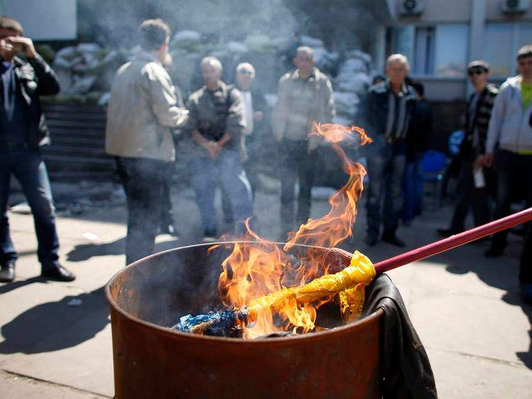 A Ukrainian flag burns outside the city hall in Mariupol, eastern Ukraine