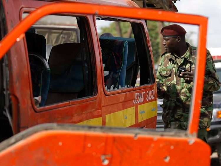 A policeman inspects a damaged public transport van at the scene of a twin explosion at the Gikomba open-air market for second-hand clothes in Nairobi