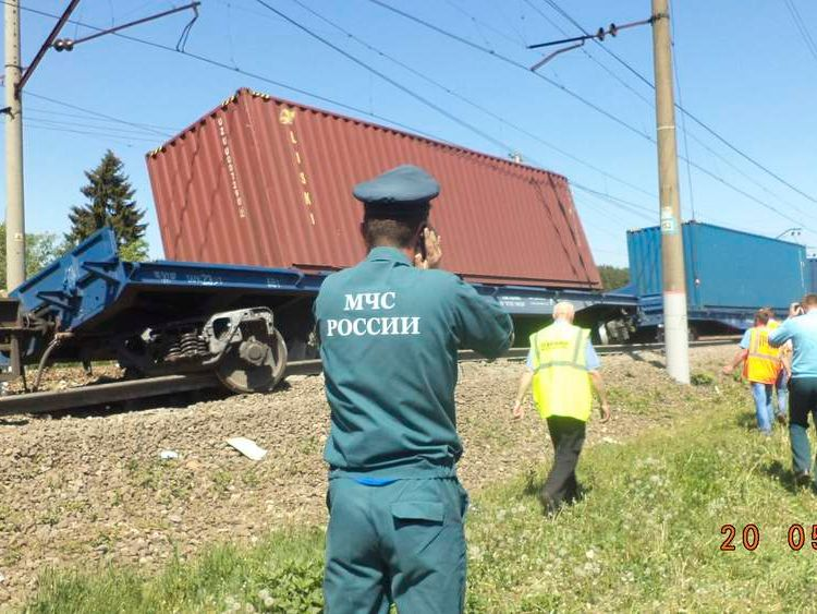 An Emergencies Ministry member speaks on a phone in front of a freight train after a collision with a passenger train in Moscow region