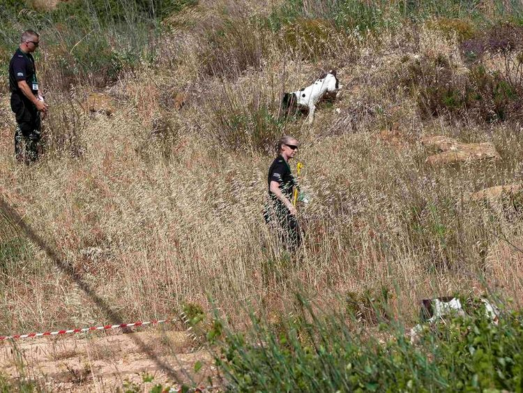 Scotland Yard detectives work with sniffer dogs at an area in Praia da Luz