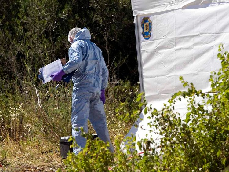 A Scotland Yard detective wearing a forensic suit works at an area during the search for missing British girl Madeleine McCann in Praia da Luz