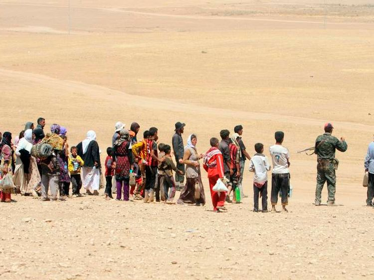 Displaced people from minority Yazidi sect, fleeing violence from forces loyal to Islamic State in Sinjar town, make way towards Syrian border, on outskirts of Sinjar mountain
