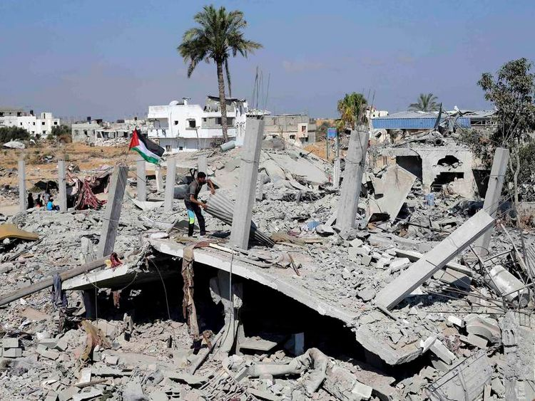 A Palestinian flag flutters as a Palestinian man searches for his belongings from the remains of his house, which witnesses said was destroyed in the Israeli offensive, during a 72-hour truce in Khan Younis