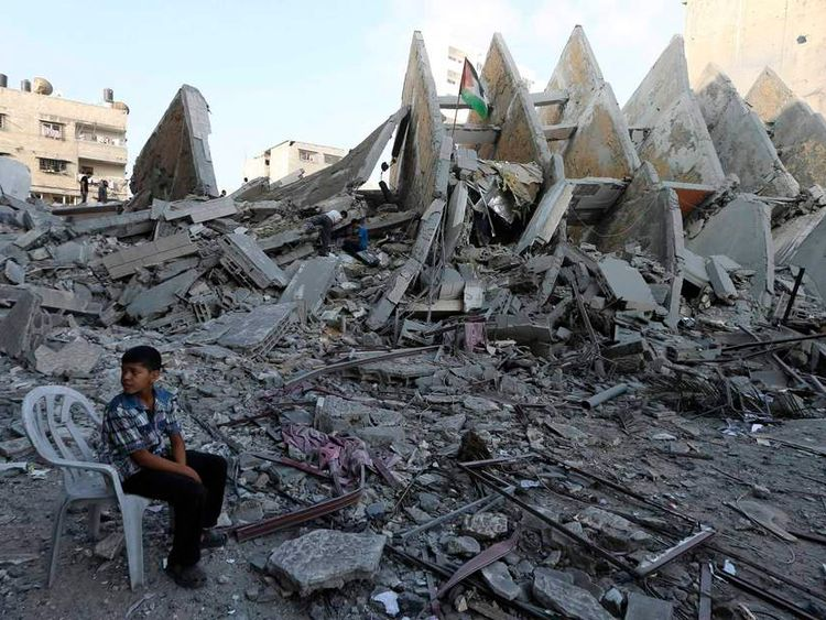 Palestinian boy sits near the remains of a tower building housing offices which witnesses said was destroyed by Israeli air strikes in Gaza City